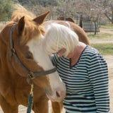 La donna senior abbraccia un cavallo quarto immagine stock