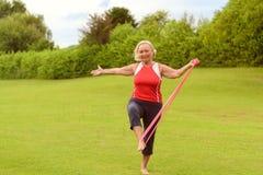 La donna senior adatta che usando la resistenza lega con la gamba Fotografia Stock