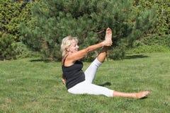 La donna senior bionda sta esercitandosi nel giardino Fotografia Stock Libera da Diritti