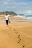 La donna senior cammina sulla spiaggia di Lumahai in Kauai immagine stock