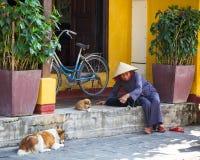 La donna senior in cappello conico sta giocando con il cucciolo sulla via fotografia stock libera da diritti