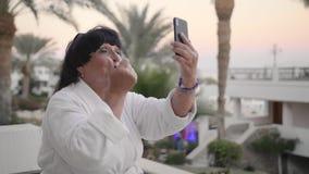 La donna senior caucasica felice in un abito bianco di Terry sta riposando su una località di soggiorno tropicale e fa una video  stock footage