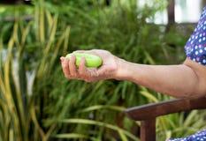 La donna senior che fa l'esercizio della mano con l'allenamento verde del cerchio fornisce Fotografie Stock Libere da Diritti