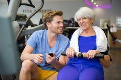 La donna senior che fa lo sport si esercita con la vettura o l'istruttore personale immagini stock libere da diritti
