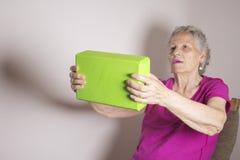 La donna senior che fa la riabilitazione si esercita con un blocco di yoga Fotografia Stock