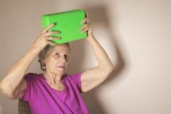 La donna senior che fa la riabilitazione si esercita con un blocco di yoga Fotografie Stock Libere da Diritti