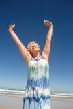 La donna senior con le armi ha sollevato la condizione contro il chiaro cielo Fotografia Stock Libera da Diritti