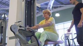 La donna senior fa per tirare sull'esercizio sull'apparecchiatura di addestramento nella palestra archivi video