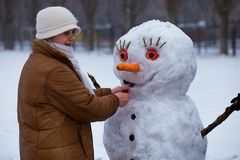 La donna senior felice scolpisce ed abbraccia un grande pupazzo di neve reale nell'inverno Immagini Stock Libere da Diritti