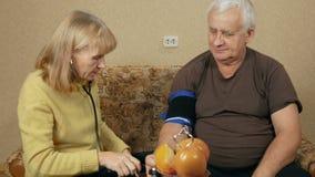 La donna senior misura la pressione sanguigna di un uomo a casa sullo strato Indossa un polsino sul vostro braccio ed ascolta video d archivio
