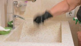 La donna senior pulisce il lavandino nel bagno della camera di albergo Usa i guanti ed il pulitore Nelle mani di una spugna video d archivio