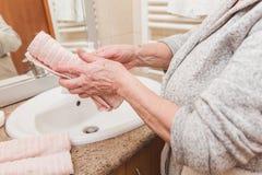 La donna senior pulisce le sue mani con un asciugamano in bagno a tempo la mattina, primo piano immagini stock