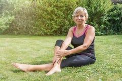 La donna senior sta rilassandosi dopo l'allungamento all'aperto Fotografia Stock