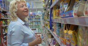La donna senior sta scegliendo l'alimento per animali domestici inscatolato circa la navata laterale del supermercato con il cane video d archivio