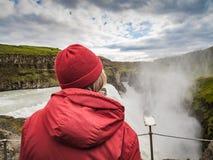 La donna senior sta stando ad una cascata di Gullfoss - Islanda Fotografia Stock Libera da Diritti