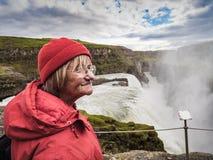 La donna senior sta stando ad una cascata di Gullfoss - Islanda Immagini Stock