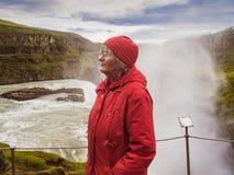 La donna senior sta stando ad una cascata di Gullfoss - Islanda Immagine Stock Libera da Diritti