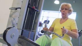 La donna senior sta tirando su sull'apparecchiatura di addestramento nella palestra stock footage