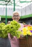 La donna senior tiene il canestro con i fiori e compra la lattuga sul segno fotografia stock