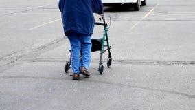 La donna senior usa un camminatore mentre cammina fuori su un parcheggio archivi video