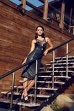 La donna sensuale con capelli scuri porta il vestito nero elegante Immagini Stock Libere da Diritti