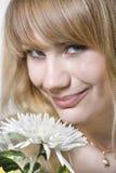 La donna sente l'odore di un fiore Fotografia Stock
