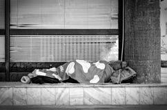 La donna senza tetto dorme sulla via Immagine Stock