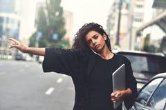 La donna seria della corsa mista utilizza un telefono, prova a prendere un taxi Immagine filtrata fotografia stock