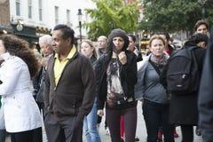La donna seria in un maglione casuale fa il suo modo attraverso la folla alla via di Liverpool immagini stock libere da diritti