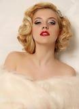 La donna sexy con capelli ricci biondi e trucco luminoso, indossa la pelliccia Fotografie Stock Libere da Diritti