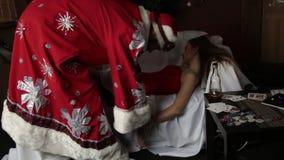 La donna sexy in costume di carnevale che si trova sul sofà, il Babbo Natale dell'infermiere femminile ubriaco prova a svegliarla archivi video
