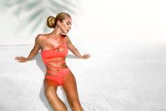 La donna sexy elegante in bikini sul corpo esile e ben fatto Sun-abbronzato sta posando vicino alla piscina Prendendo il sole dal immagini stock libere da diritti