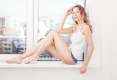 La donna sexy si è vestita nei bicchierini e nel bianco del denim che si trovano vicino alla finestra Fotografia Stock Libera da Diritti