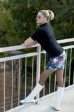 La donna sexy in stivali bianchi e una minigonna sul ponte guardano Fotografia Stock