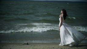La donna sexy in un vestito bianco sta sul mare Il vestito fluttua nel movimento lento del vento archivi video