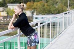 La donna sexy in una minigonna sul ponte che guarda lontano, railwa Fotografie Stock