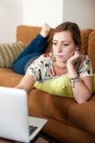 La donna si è distesa con il suo computer portatile. Fotografie Stock