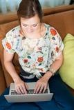 La donna si è distesa con il suo computer portatile. Immagini Stock Libere da Diritti