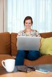 La donna si è distesa con il suo computer portatile. Immagine Stock