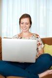 La donna si è distesa con il suo computer portatile. Fotografia Stock Libera da Diritti