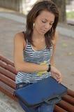 La donna si è seduta sul banco con il dispositivo di piegatura fotografia stock libera da diritti