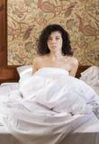 La donna si è svegliata a letto dopo la notte agitata Immagine Stock