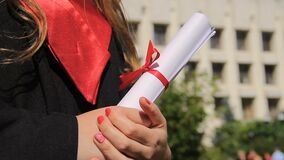 La donna si è vestita in diploma della tenuta dell'abito di graduazione, esaminante il futuro felice stock footage