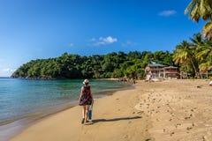 La donna si è vestita in un costume ed in un cappello che cammina in una spiaggia tropicale in Trinidad e Tobago immagine stock