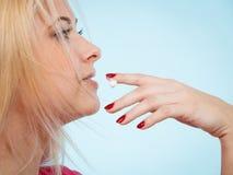 La donna si applica la crema del balsamo di labbro alle sue labbra Fotografia Stock