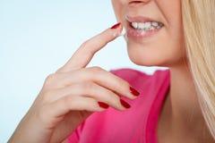 La donna si applica la crema del balsamo di labbro alle sue labbra Fotografia Stock Libera da Diritti