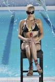 La donna si distende e beve il coctail alla piscina Immagine Stock