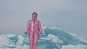 La donna si diverte durante la passeggiata dell'inverno contro fondo di ghiaccio del lago congelato La ragazza sta divertendo, ri stock footage