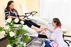 La donna si esercita nel pedicure che cattura la cura dei piedi fotografia stock libera da diritti