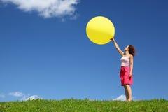 La donna si leva in piedi su erba ed inizia la sfera gonfiabile immagine stock